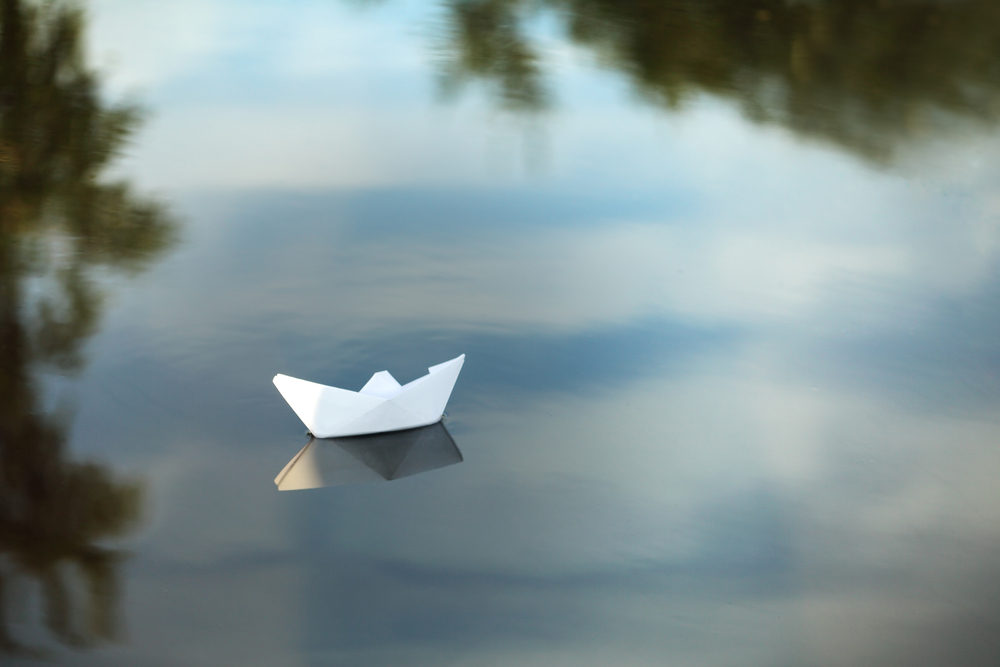 Papierschiff auf Fluss als Sinnbild für Rechnungsfluss und Rechnungen digitalisieren