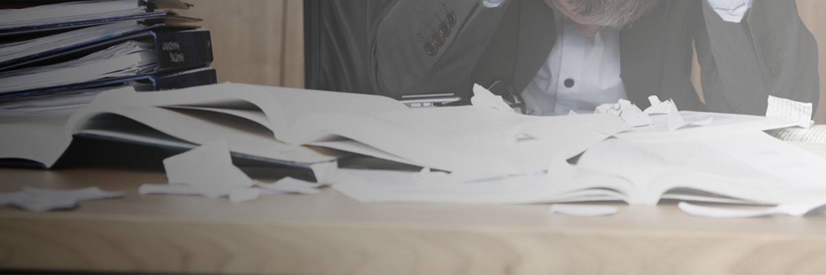 Vertragsmanagement in SharePoint Tisch mit Papierstapel