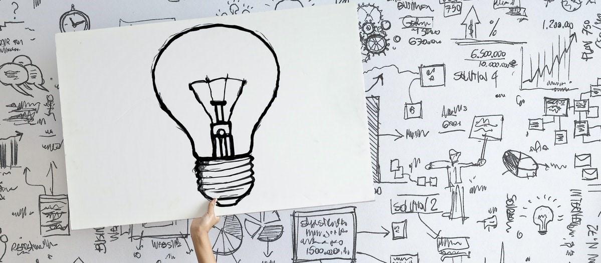 Glühbirne und Infografiken als Sinnbild für Geschäftsprozesse.