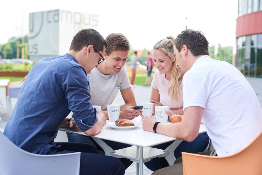 d-velop Mitarbeiter draußen Sitzgruppe mit Smartphone und Kaffee