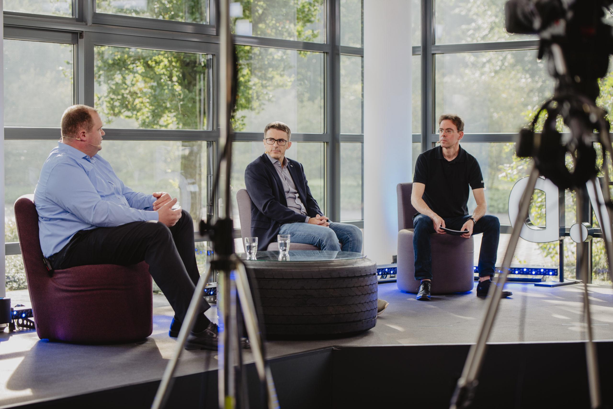 Holger Lesting und Michael Schoeller von Smitz Cargobull berichten Moderator Stefan Olschewski von der Migration von 60 Mio Dokumenten in die Cloud (vlnr)